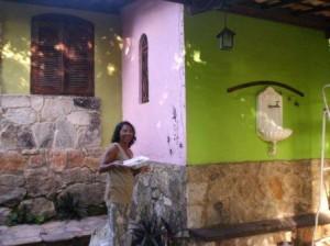 Maria, avó de aluna e amiga da Vila, na pintura da escola